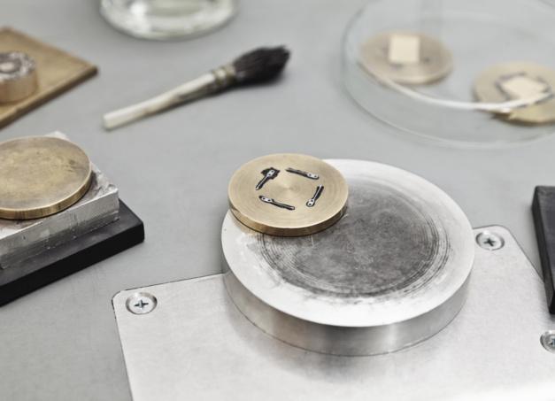 Polissage en noir : quatre ressorts de cliquet sont fixés à la cire d'abeille sur un anneau de laiton. Sur une plaque en étain, l'horloger polit la surface des ressorts avec de la pâte à polir jusqu'à ce que l'étain et la pâte deviennent noirs.