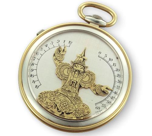 """1930 - Montre de poche """"Bras en l'air"""". Or jaune et or gris 18K, cadran argenté avec magicien chinois or jaune et émail noir, indiquant les heures et les minutes avec ses bras. Affichage rétrogradant et à la demande, par pression sur un poussoir or gris."""