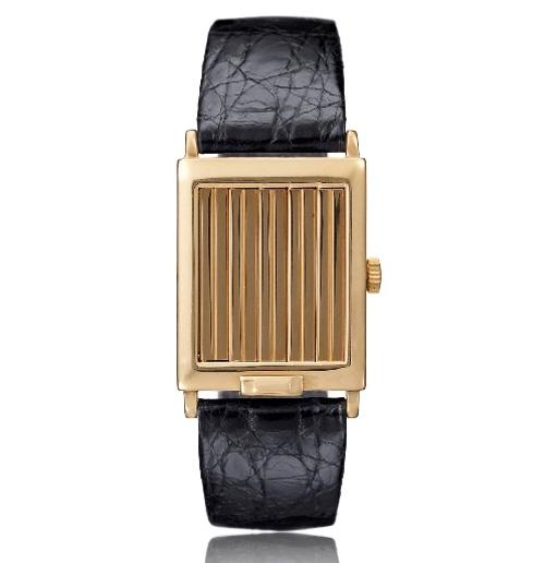 1929 - Montre-bracelet homme à volets. Or jaune18K, cadran argenté, chiffres arabes or jaune. Ouverture des volets au moyen d'une glissière sur la lunette.